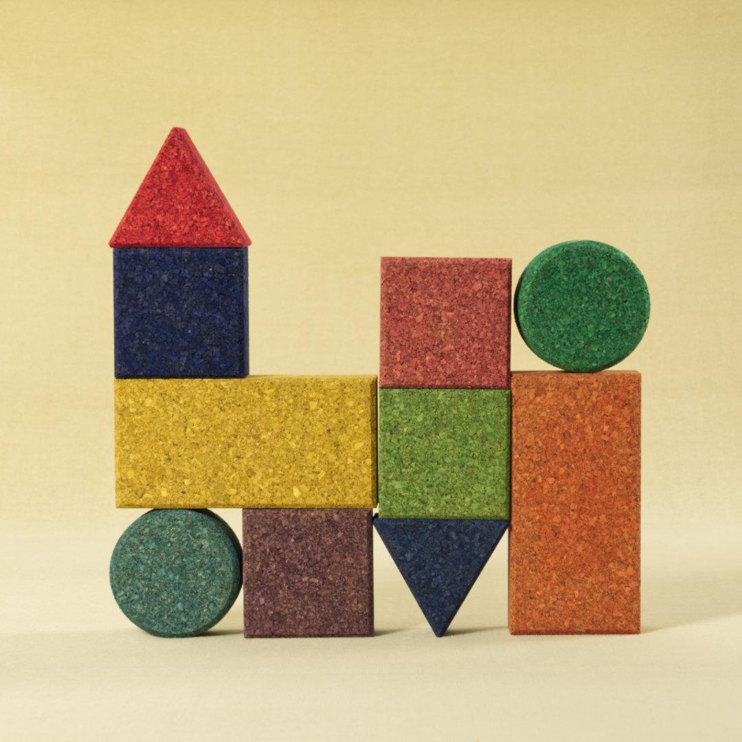 10-teiliges Set aus Korkbausteinen in verschiedenen Formen und Farben, zu einer Form gestapelt