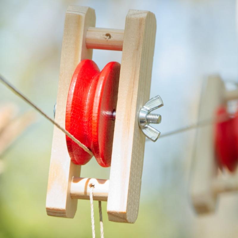 Detail Flaschenzug Rolle aus Holz in rot und naturfarben mit Hanfschnur