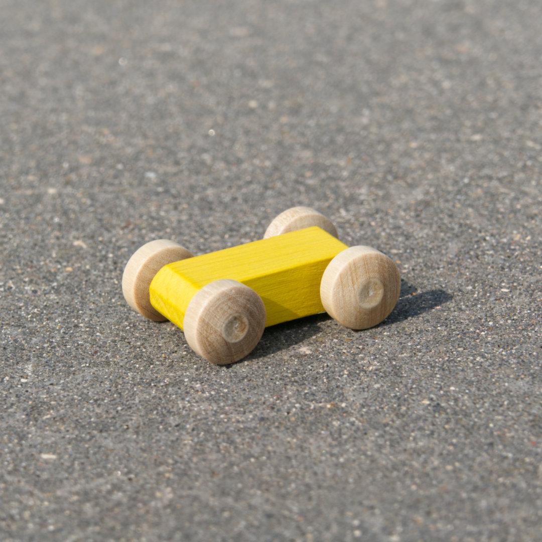 Kleines, leuchtend gelbes, reduziertes Holzfahrzeug mit naturfarbenen Holzreifen, fahrbar