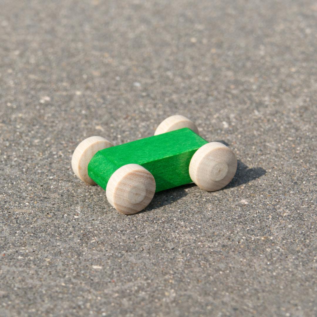 Kleines, leuchtend grünes, reduziertes Holzfahrzeug mit naturfarbenen Holzreifen, fahrbar