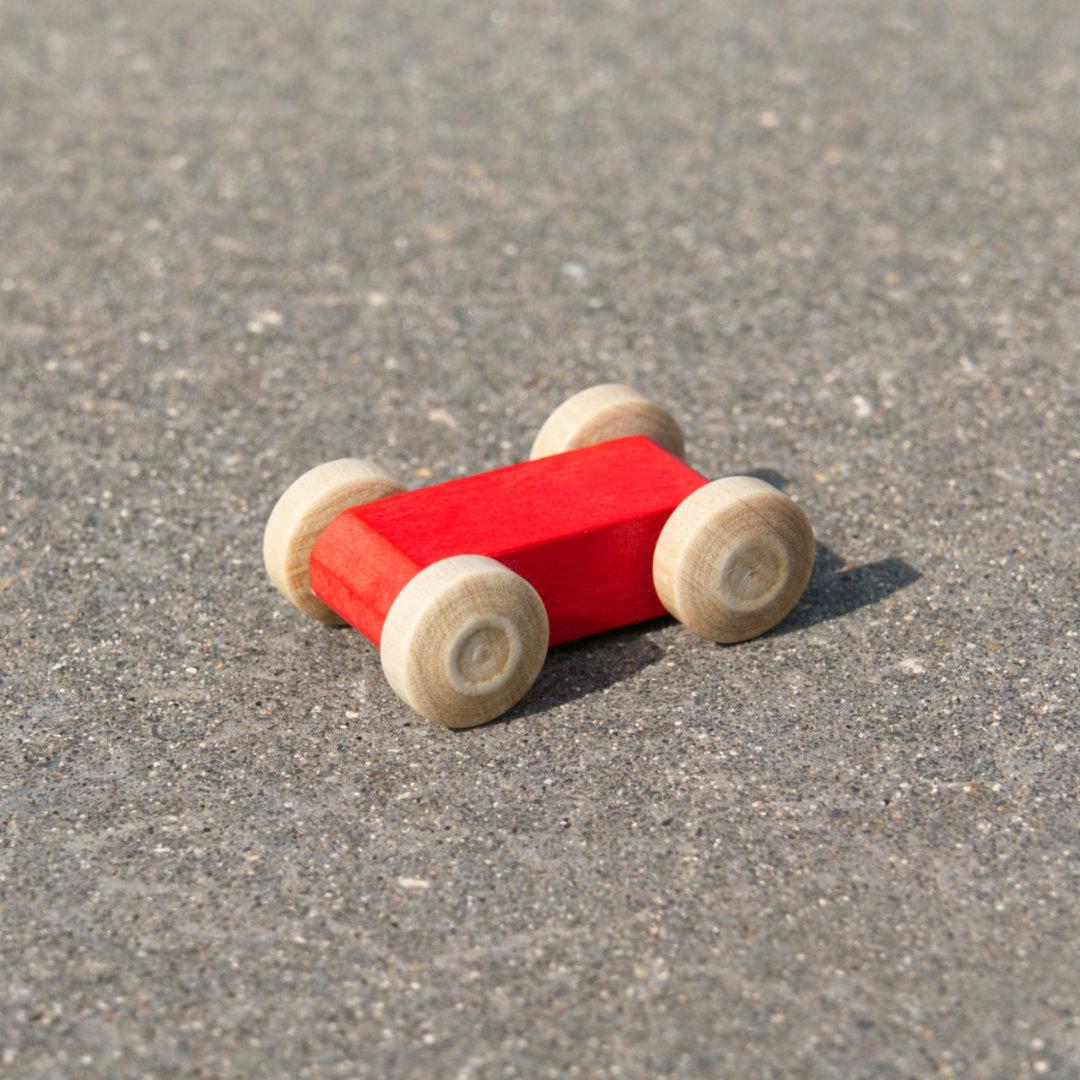 Kleines, leuchtend rotes, reduziertes Holzfahrzeug mit naturfarbenen Holzreifen, fahrbar