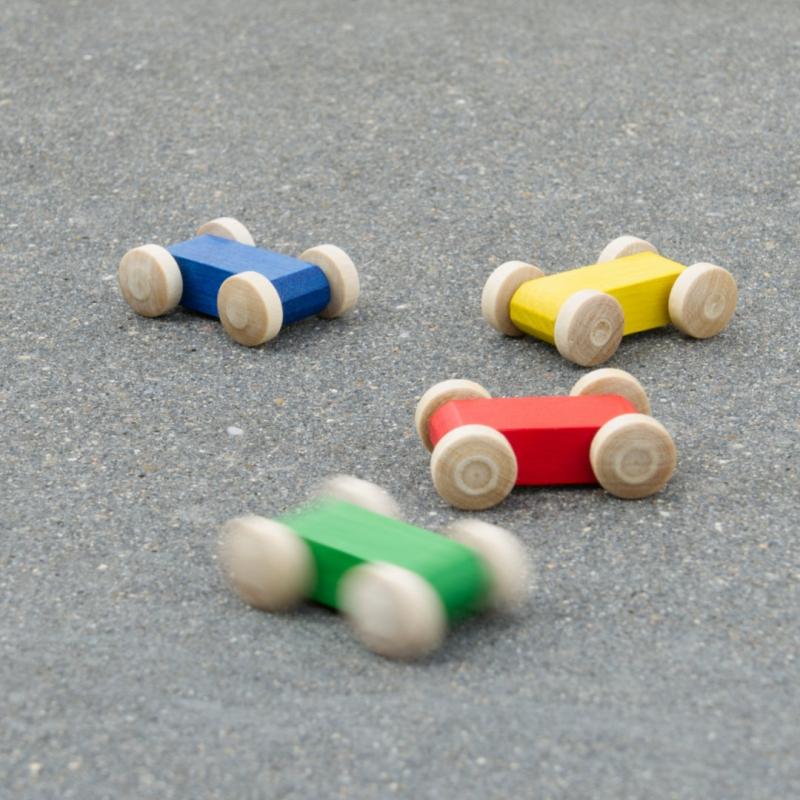 Komposition aus kleinen Holzfahrzeug-Flitzern in bunten Farben