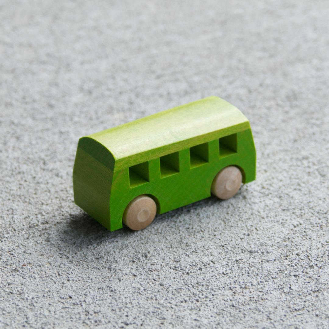 Grüner Holzspielzeug-Bus mit naturfarbenen Holzreifen