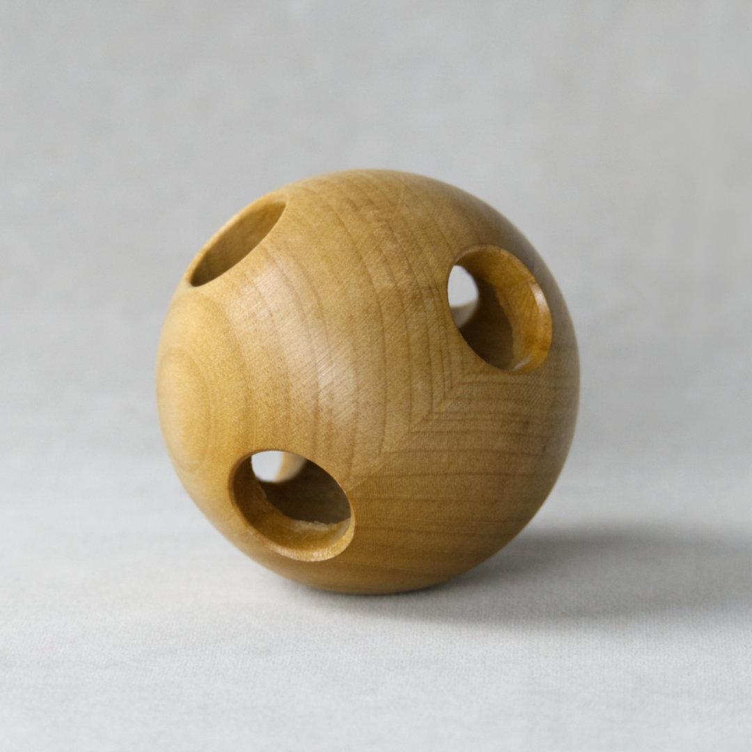 Greifling aus Holz in Ballform mit kreisrunden Öffnungen