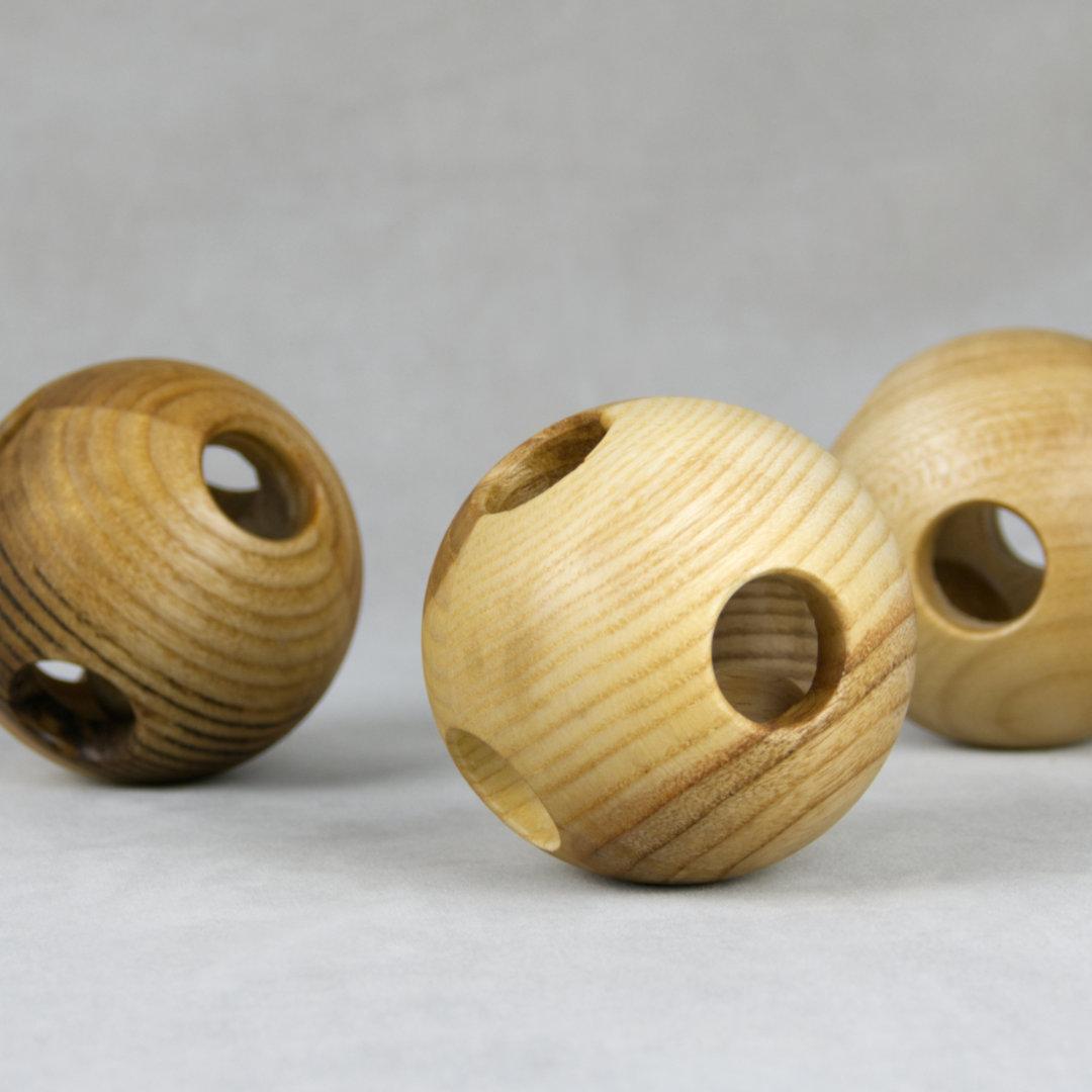 Greiflinge aus Holz in Ballform mit kreisrunden Öffnungen mit unterschiedlichen Holzmustern