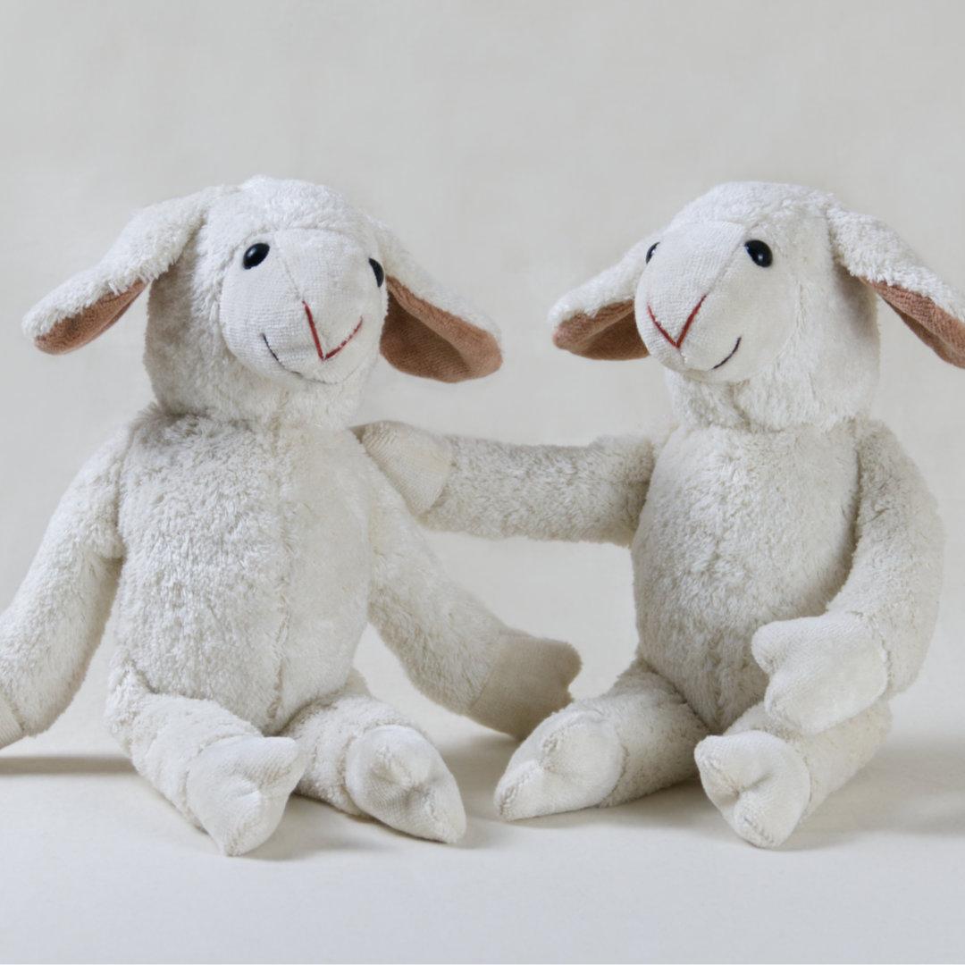 Zwei befreundete Stofftier-Schafe halten sich im Arm
