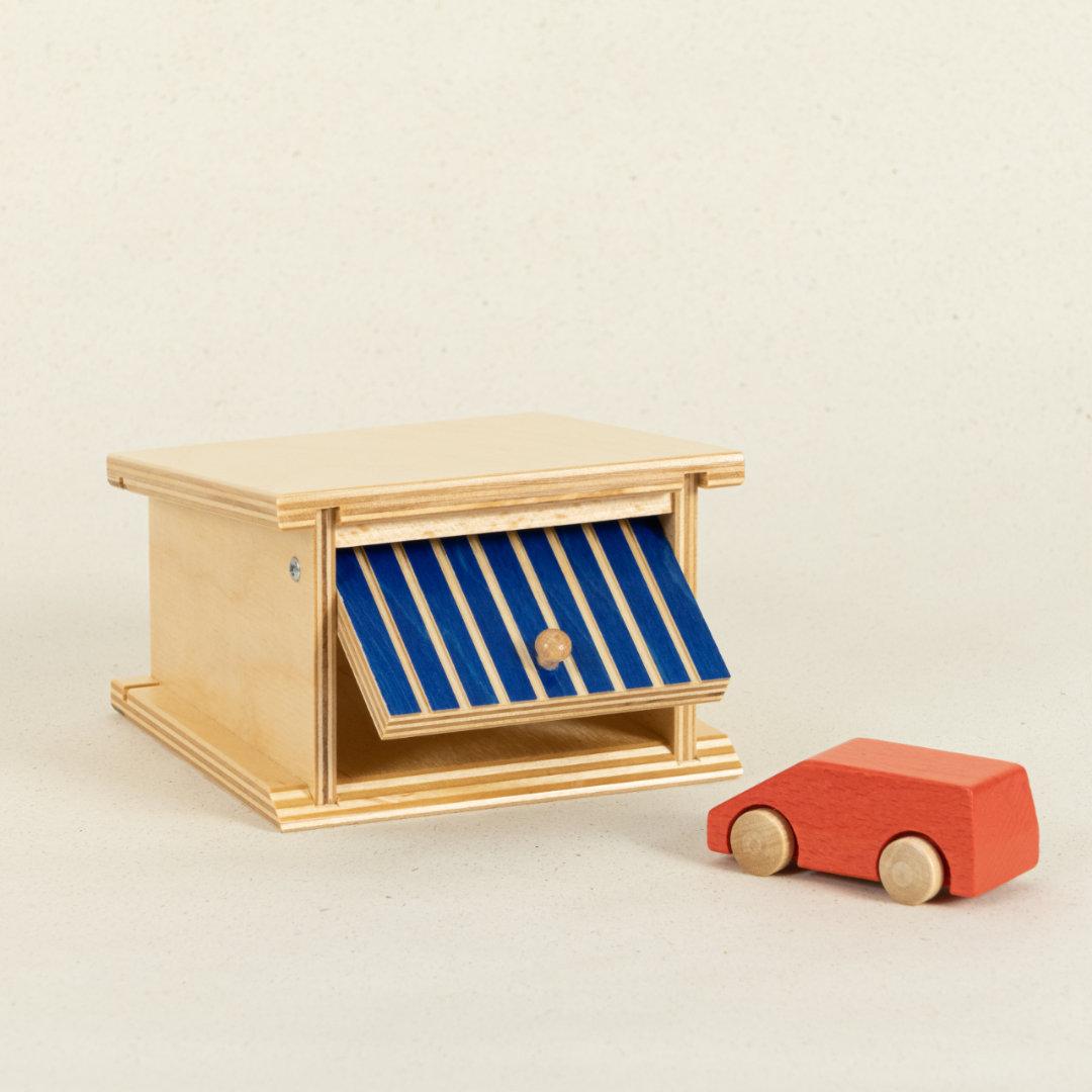Garage aus Holz mit blau-gestreiftem Kipptor