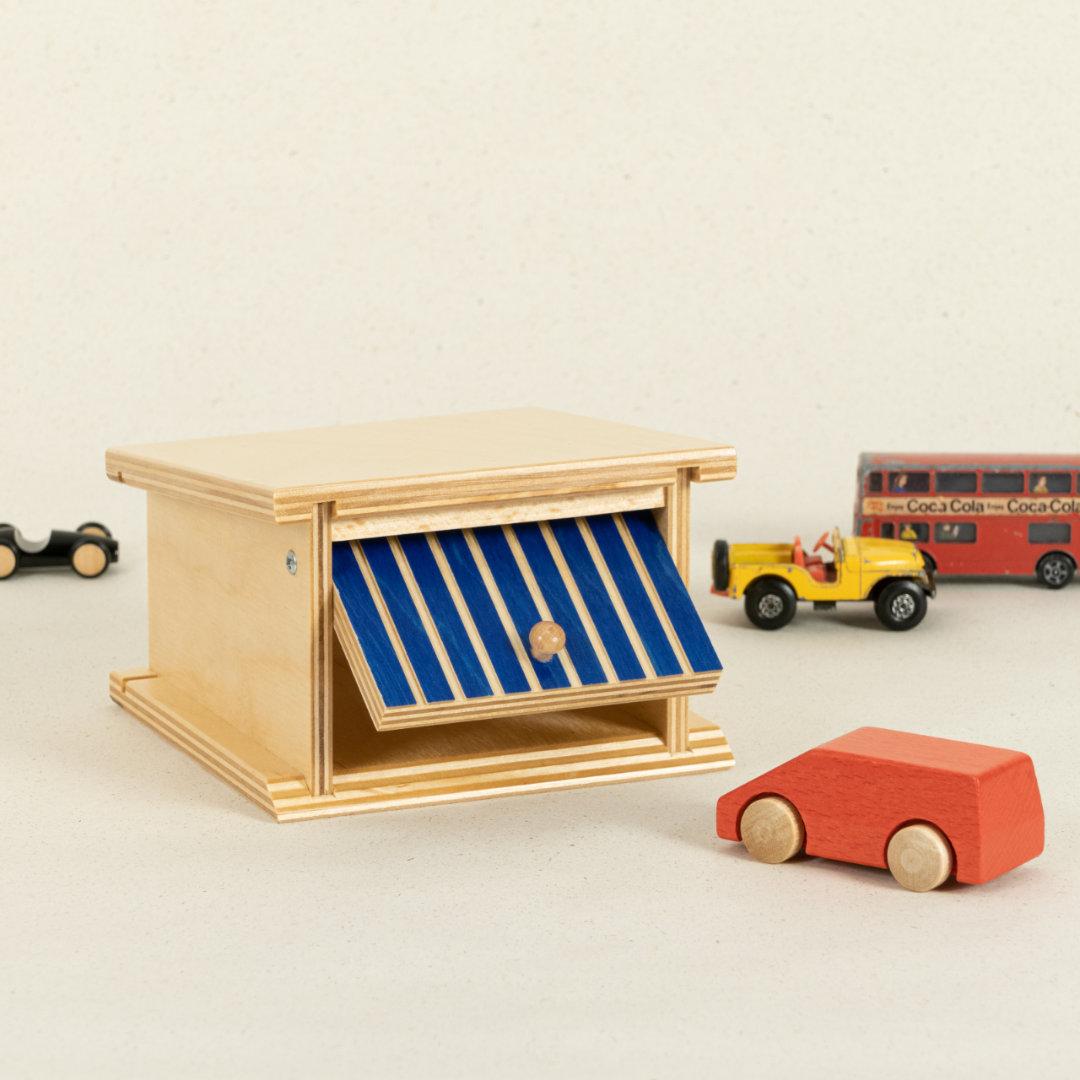 Garage aus Holz mit blau-gestreiftem Kipptor und Platz für zwei Autos