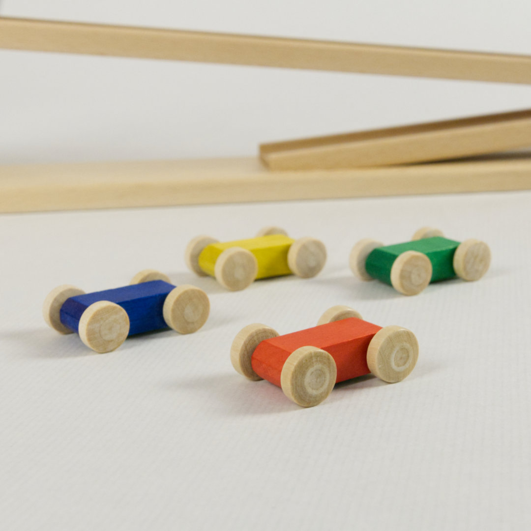 Detail vier bunte Flitzer aus Holz in den Farben rot, grün, blau und gelb