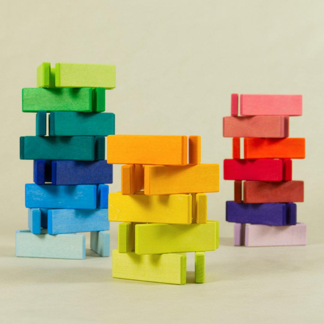 Naturholz Bausteine, lasiert in Regenbogenfarben, als Turm aufgebaut