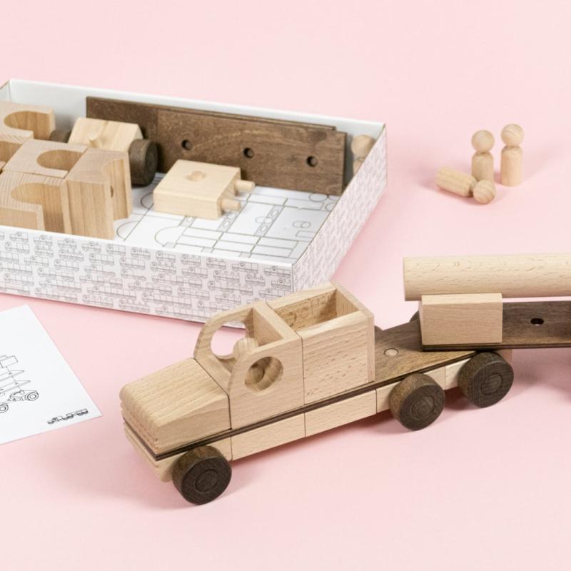 Holzelemente die zu einem Truck zusammengebaut sind, weitere Bauteile mit Bauanleitung aus Papier in einem Karton.