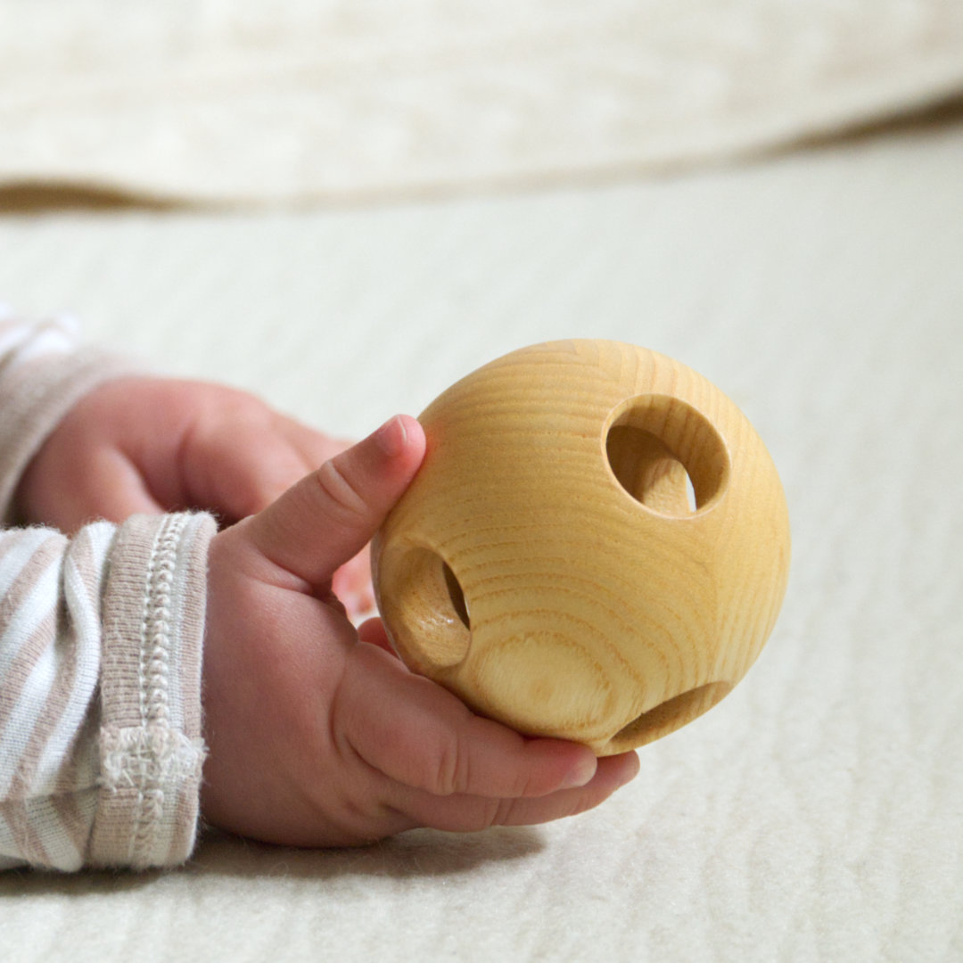 Der Greifling aus Holz liegt angenehm in der Kinderhand