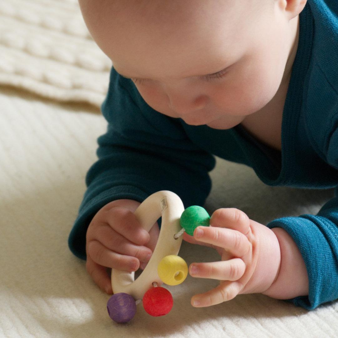 Baby spielt mit den bunten Perlen des Beissrings