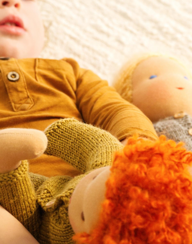 Kleinkind spielt mit Stoffpuppen