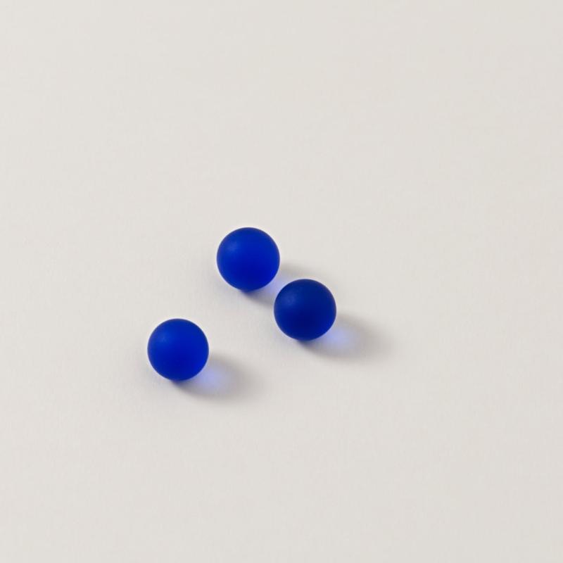 Drei matte, blaue Murmeln