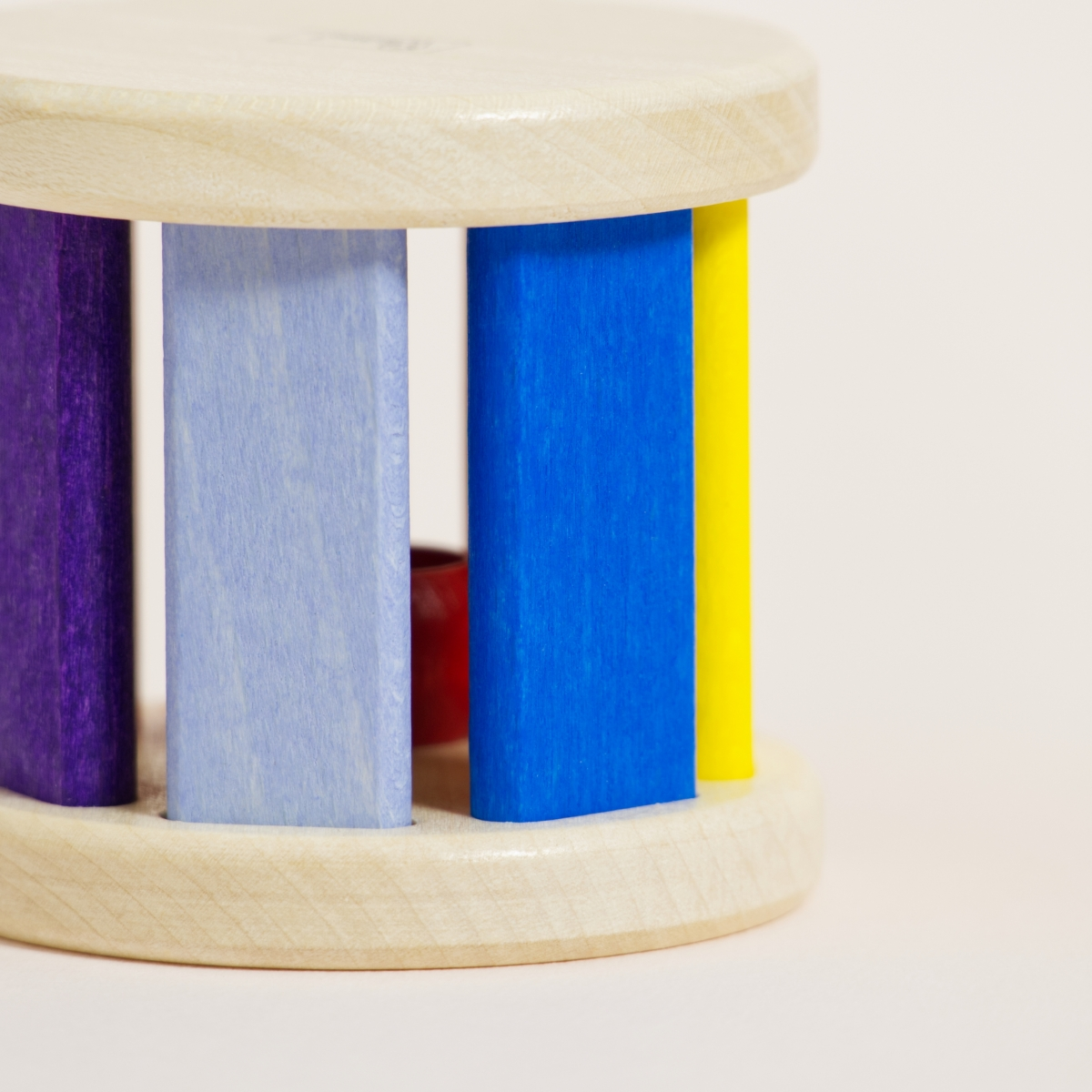 Klangrolle aus Ahornholz mit bunt gefärbten Stäben in verschiedenen Farben von Rot bis Gelb zu Blau und Lila, Detailaufnahme Holzstruktur erkennbar
