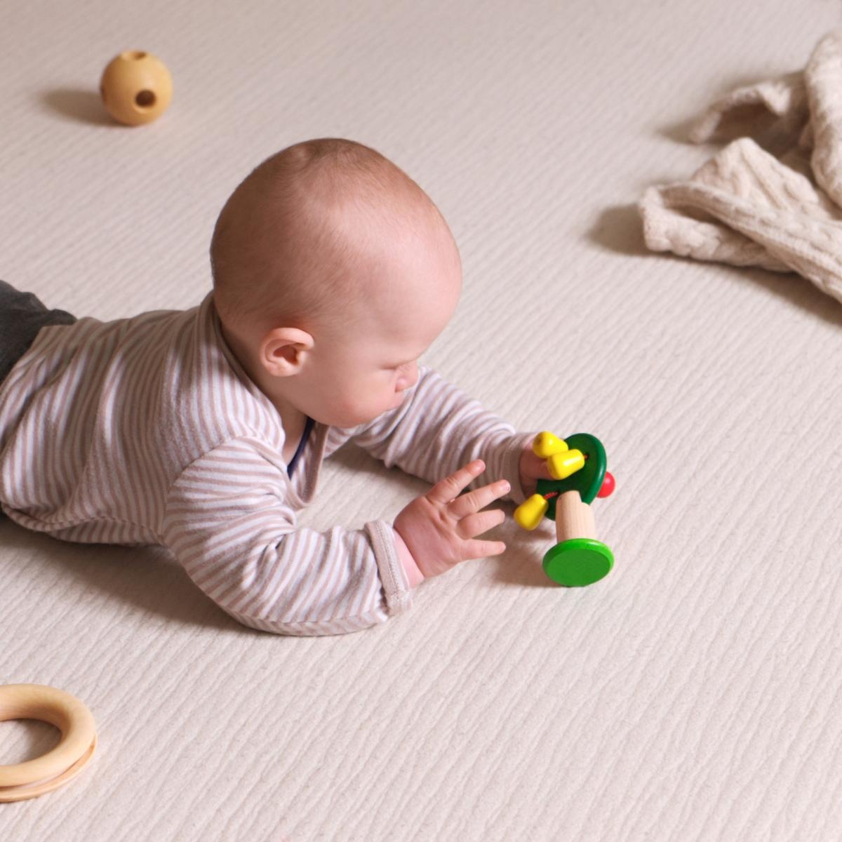 Baby spielt mit den gelben Birnen des Obstbäumchens