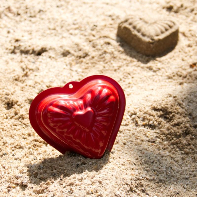 Rote Herz-Form aus Metall im Sand