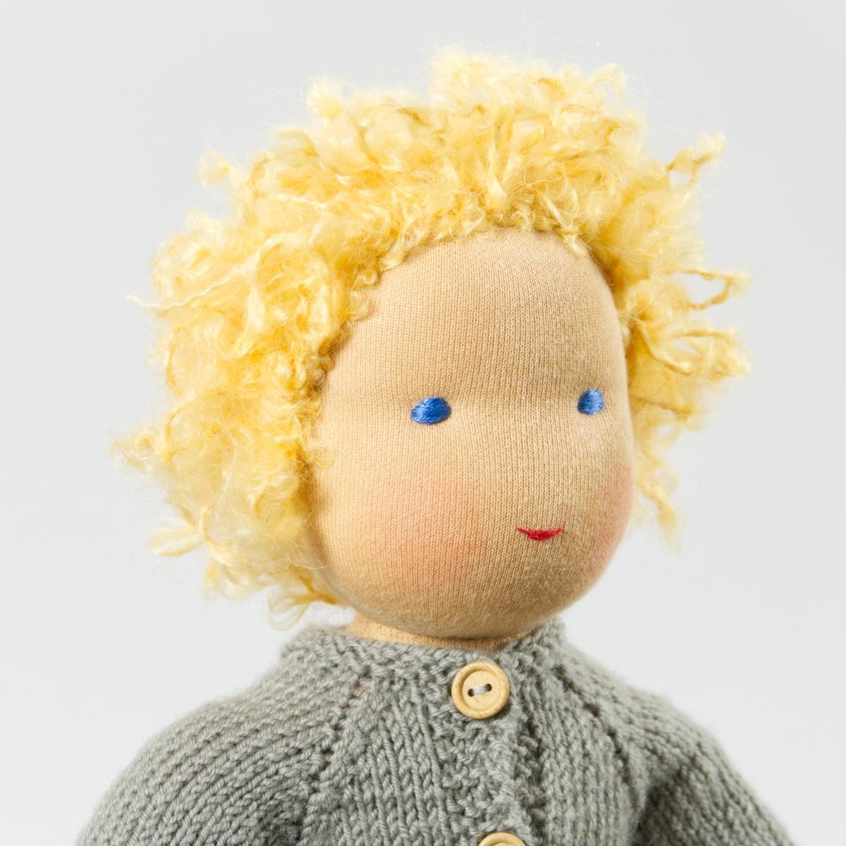 Puppe mit hellem Hautton nach Waldorf-Art, kurze blonde Haare, gekleidet in grauen Strickanzug