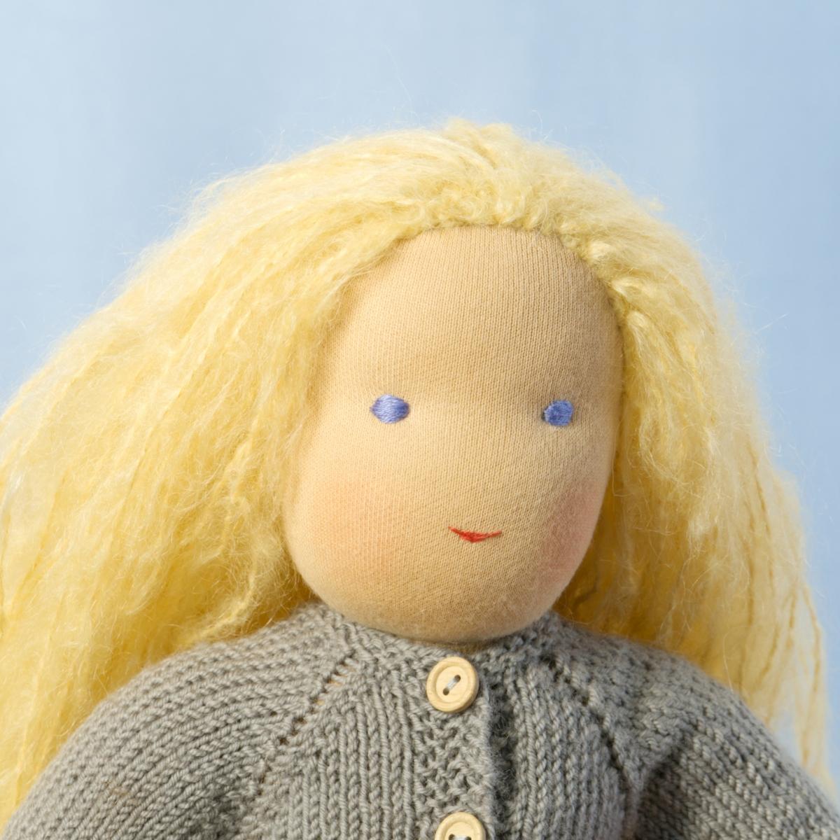 Puppe mit hellem Hautton nach Waldorf-Art, offene lange blonde Haare, gekleidet in grauen Strickanzug