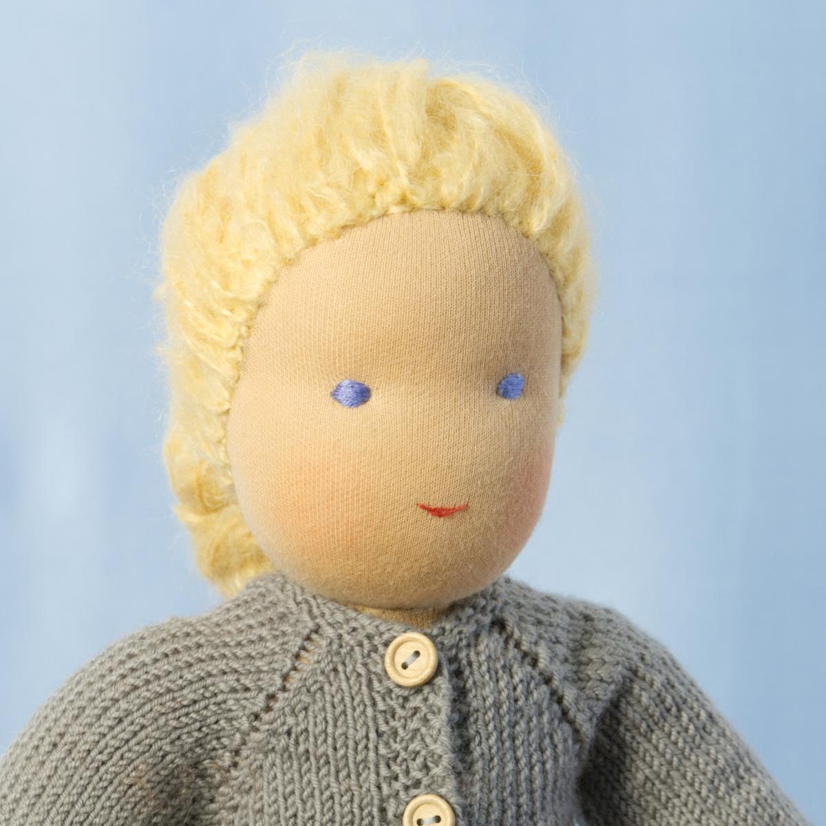 Puppe mit hellem Hautton nach Waldorf-Art, geflochtene lange blonde Haare, gekleidet in grauen Strickanzug