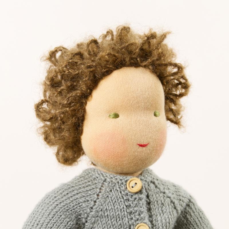 Puppe mit hellem Hautton nach Waldorf-Art, kurze braune Haare, gekleidet in grauen Strickanzug