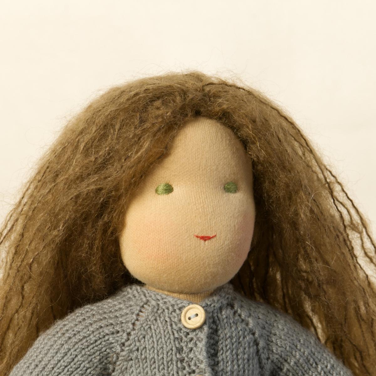 Puppe mit hellem Hautton nach Waldorf-Art, offene lange braune Haare, gekleidet in grauen Strickanzug