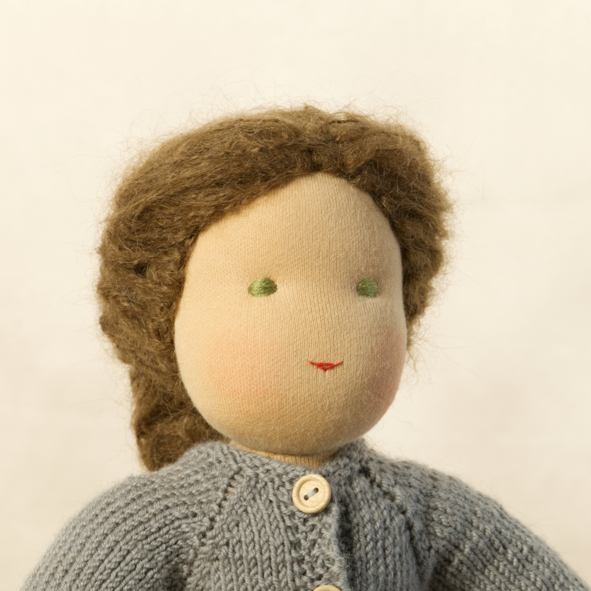 Puppe mit hellem Hautton nach Waldorf-Art, geflochtene lange braune Haare, gekleidet in grauen Strickanzug