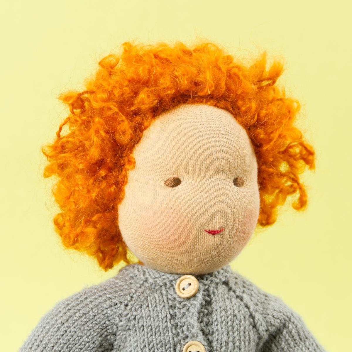 Puppe mit hellem Hautton nach Waldorf-Art, kurze rote Haare, gekleidet in grauen Strickanzug