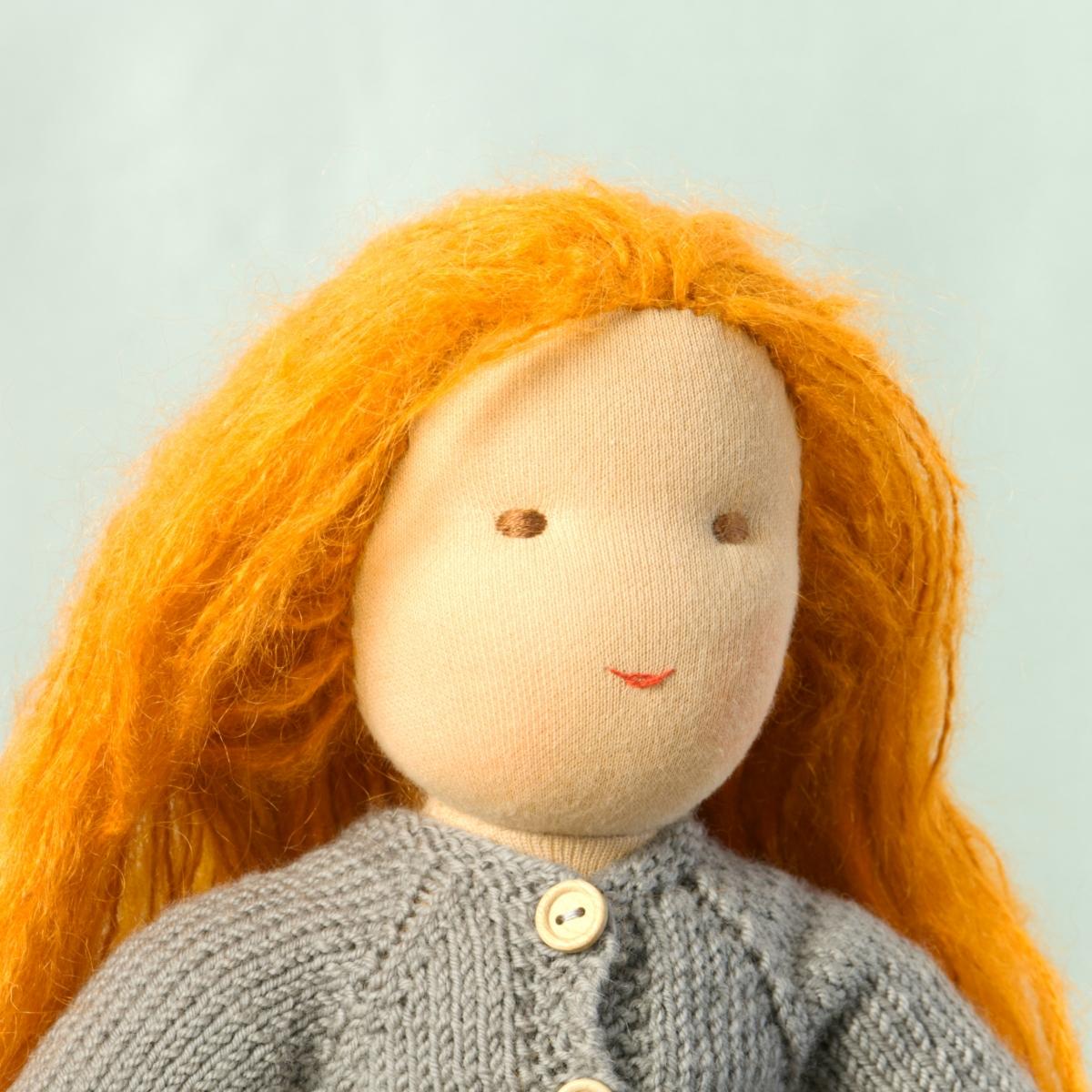 Puppe mit hellem Hautton nach Waldorf-Art, offene lange rote Haare, gekleidet in grauen Strickanzug