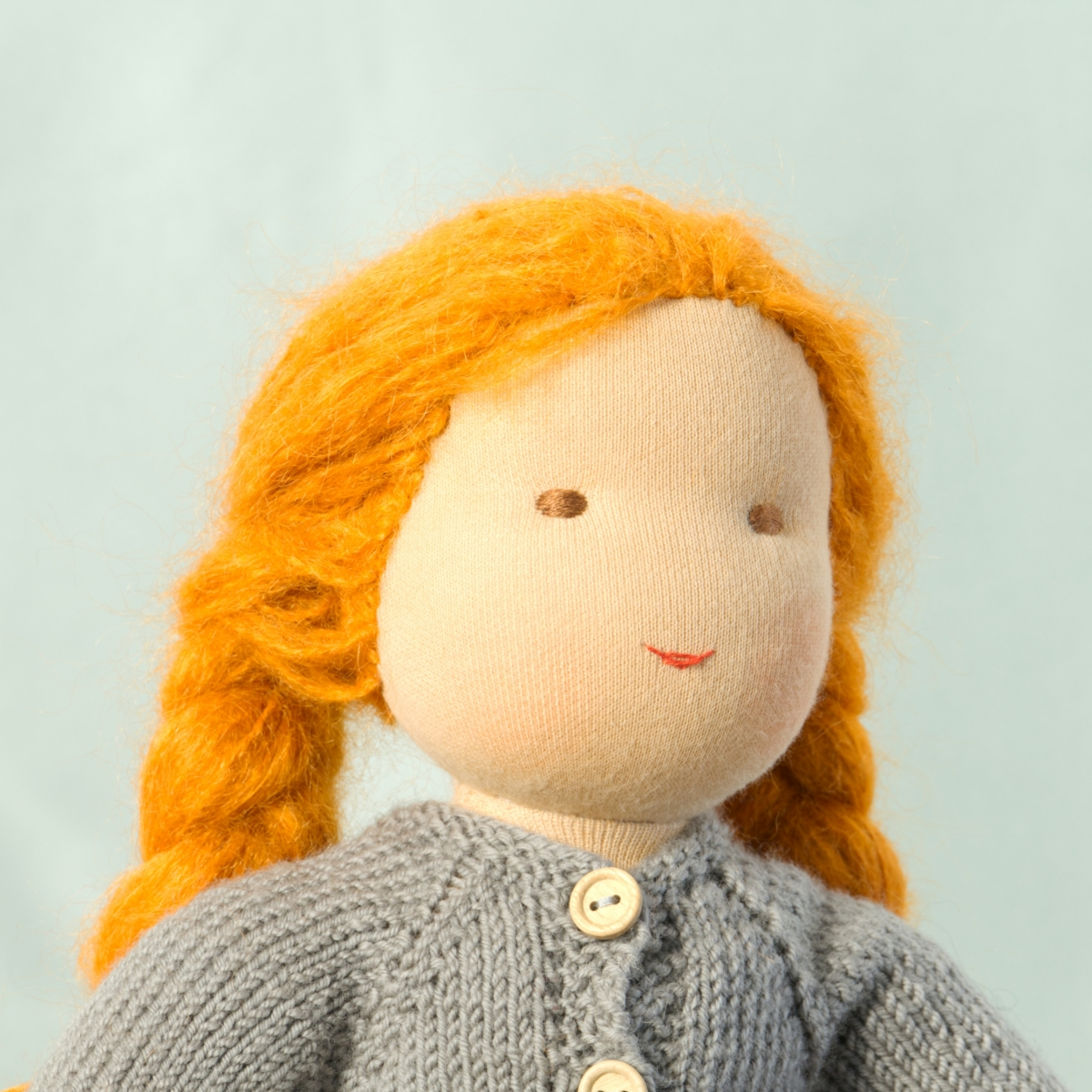Puppe mit hellem Hautton nach Waldorf-Art, geflochtene lange rote Haare, gekleidet in grauen Strickanzug