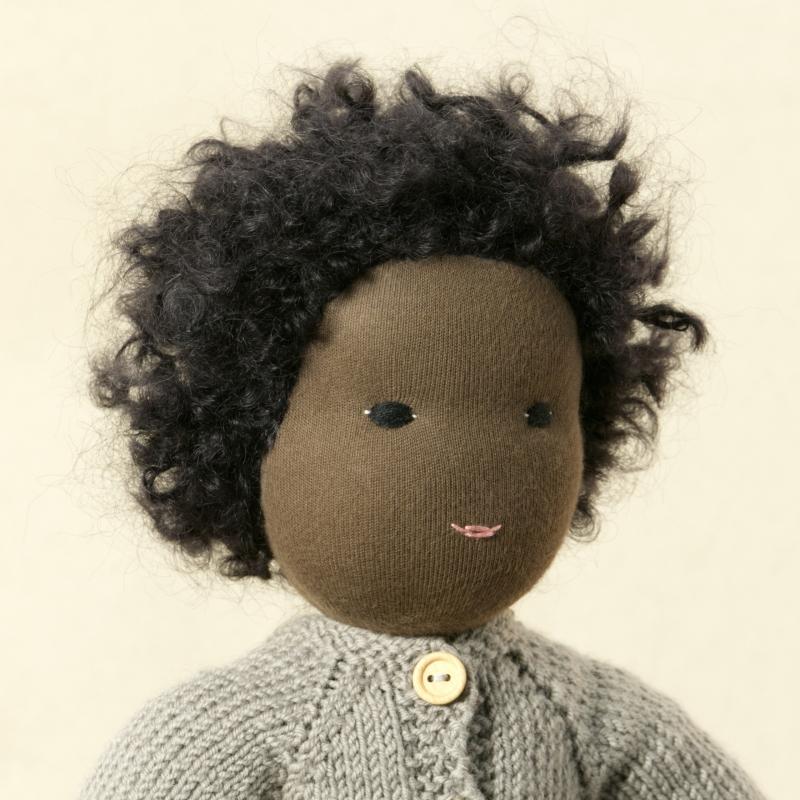 Puppe mit dunklem Hautton nach Waldorf-Art, kurze schwarze Haare, gekleidet in grauen Strickanzug