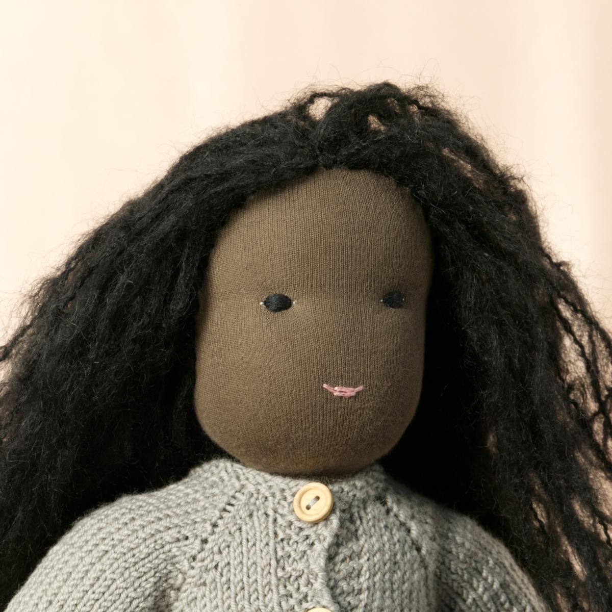 Puppe mit dunklem Hautton nach Waldorf-Art, offene lange schwarze Haare, gekleidet in grauen Strickanzug