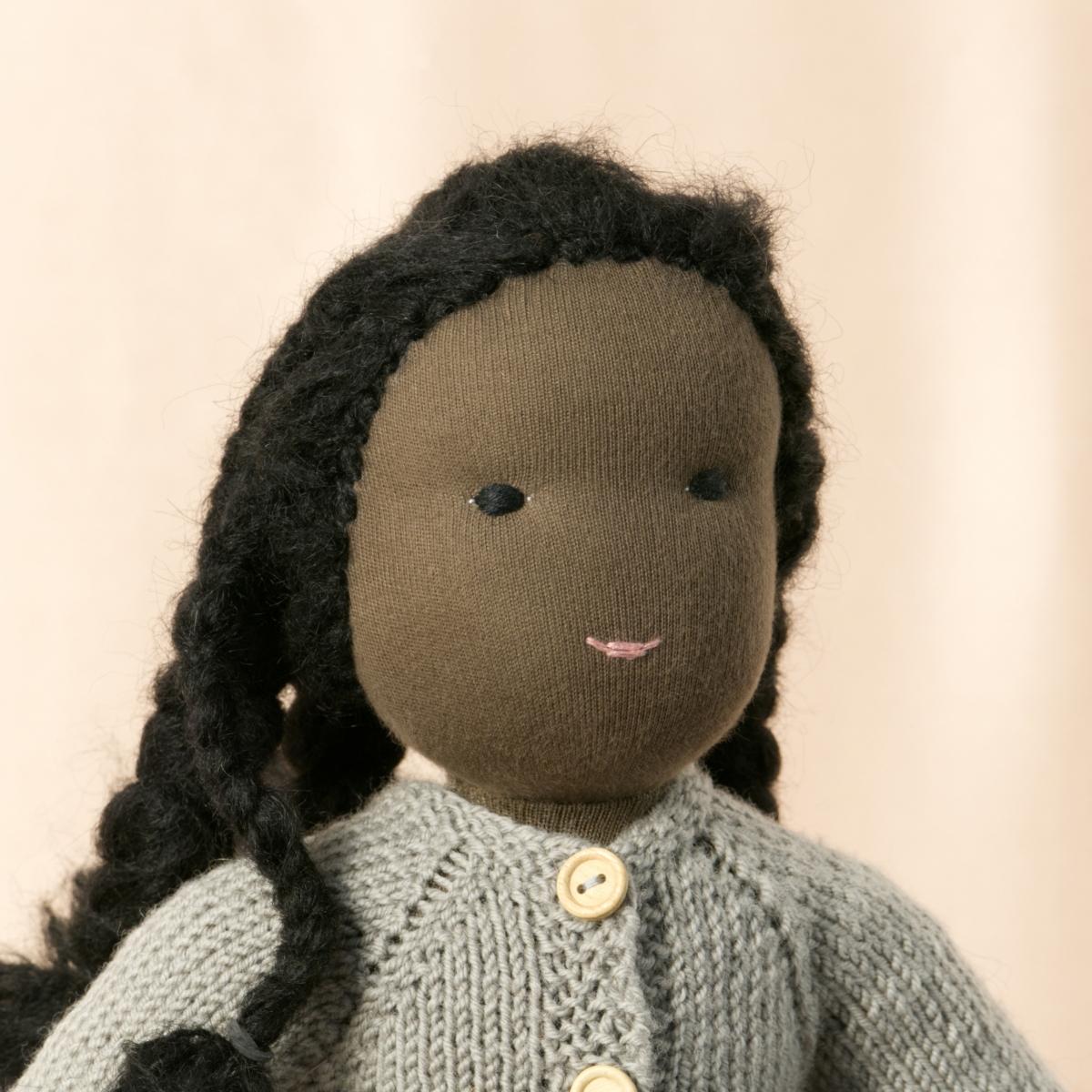 Puppe mit dunklem Hautton nach Waldorf-Art, geflochtene lange schwarze Haare, gekleidet in grauen Strickanzug