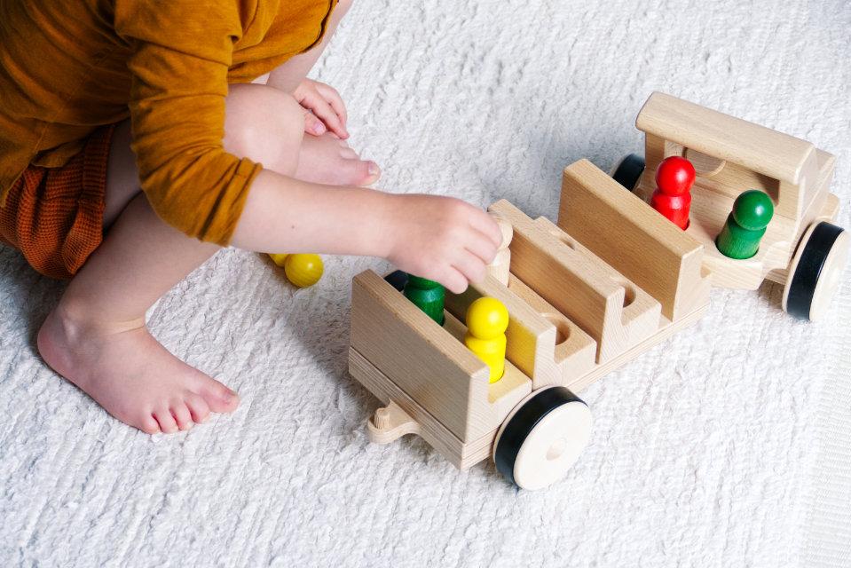 Kleinkind spielt mit Holz-Fahrzeug Typ Bus mit mehreren bunten Holzfiguren