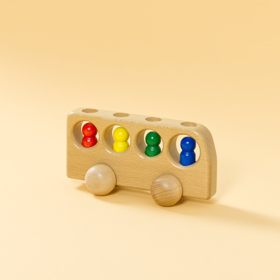 Holz-Bus aus naturbelassenem Buchenholz und vier bunten Holz-Figuren in Rot, Gelb, Grün und Blau darin