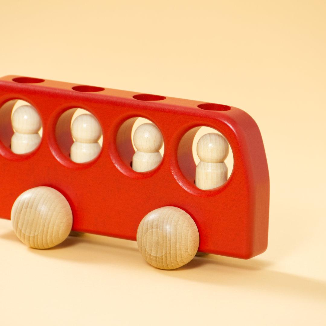 Holz-Bus aus gefärbtem Buchenholz in Rot und vier naturbelassenen Holz-Figuren darin