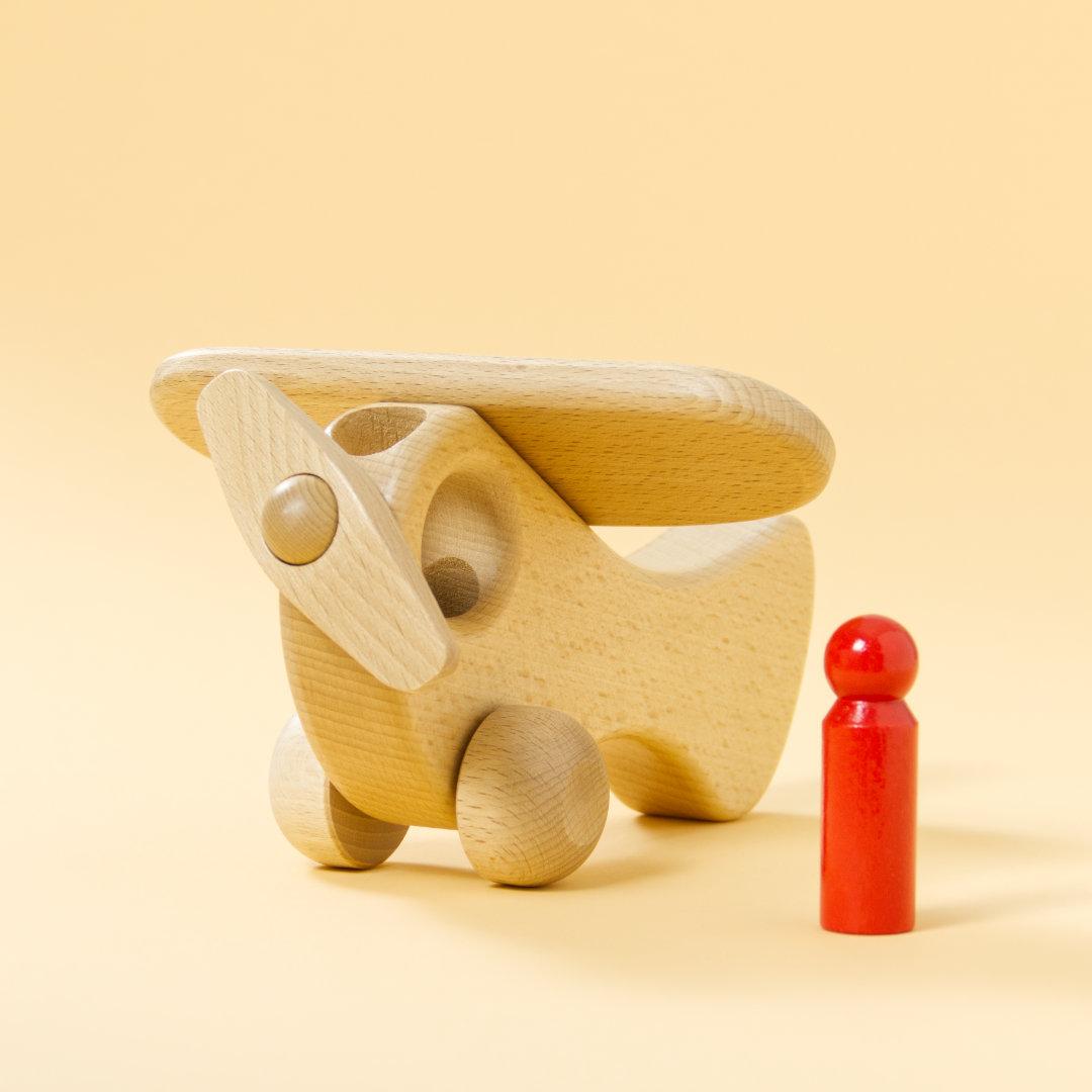 Holz-Flugzeug aus naturbelassenem Buchenholz und roter Holz-Figur