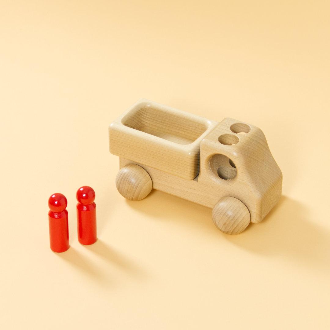 Lieferwagen aus Buchenholz, natur, mit abgerundeter Formensprache. Offene Ladefläche, Fahrerkabine mit zwei kegelförmigen, roten Figuren, die Figuren stehen, über Löcher im Dach der Fahrerkabine können sie einsteigen.