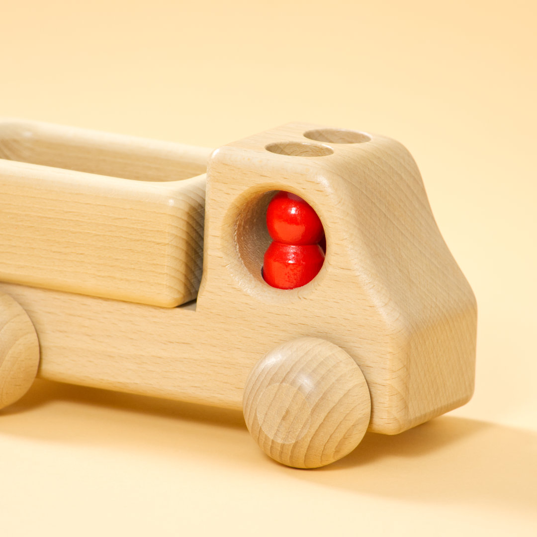 Lieferwagen aus Buchenholz, natur, mit abgerundeter Formensprache. Offene Ladefläche, Fahrerkabine mit zwei kegelförmigen, roten Figuren.