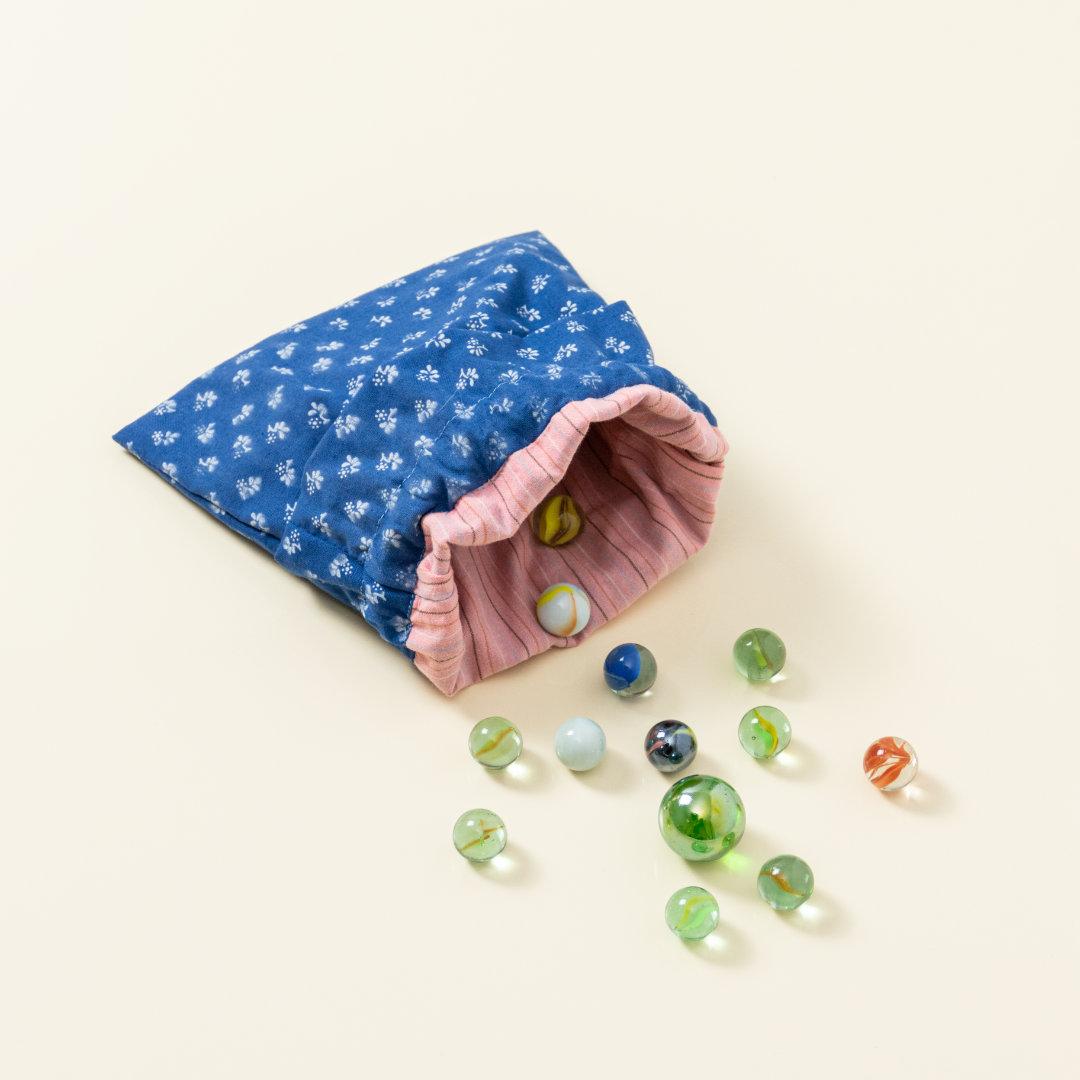 Hand-genähtes Murmelsäckchen mit Blumen-Muster in Blau-Weiß außen und rosa gestreift innen, geöffnet, inklusive einem individuellem Set aus einer großen Glas-Murmel und zwölf kleinen Glas-Murmeln
