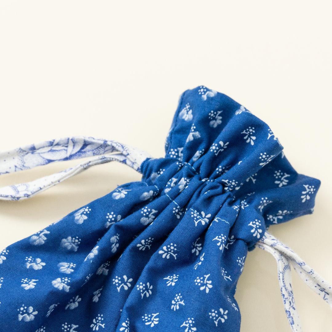 Hand-genähtes Murmelsäckchen mit Blumen-Muster in Blau-Weiß außen und rosa gestreift innen, geschlossen, inklusive einem individuellem Set aus einer großen Glas-Murmel und zwölf kleinen Glas-Murmeln, Detailaufnahme Bund Säckchen