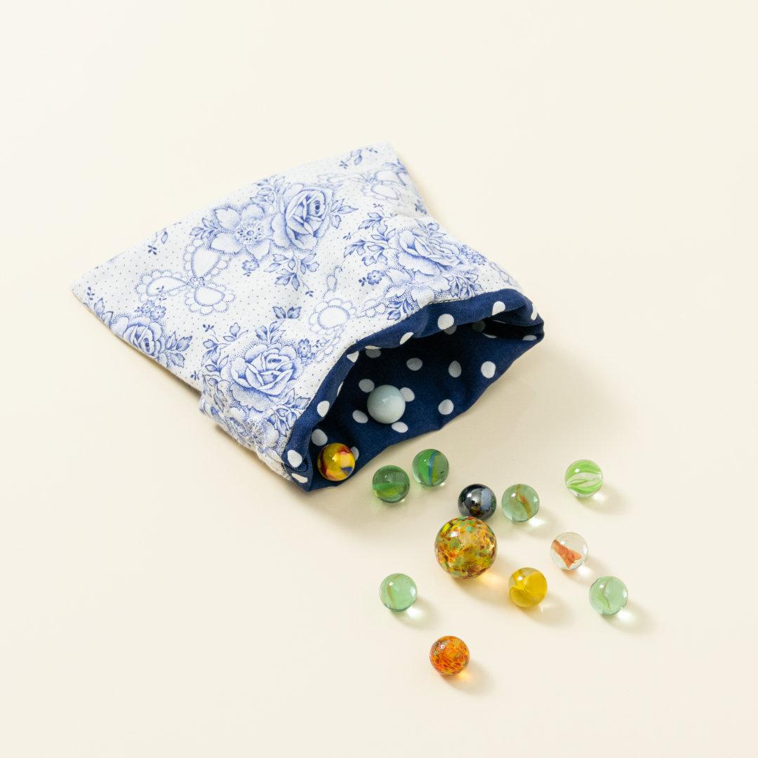 Hand-genähtes Murmelsäckchen mit Blumen-Muster in Weiß-Blau außen und gepunktet innen, geöffnet, inklusive einem individuellem Set aus einer großen Glas-Murmel und zwölf kleinen Glas-Murmeln