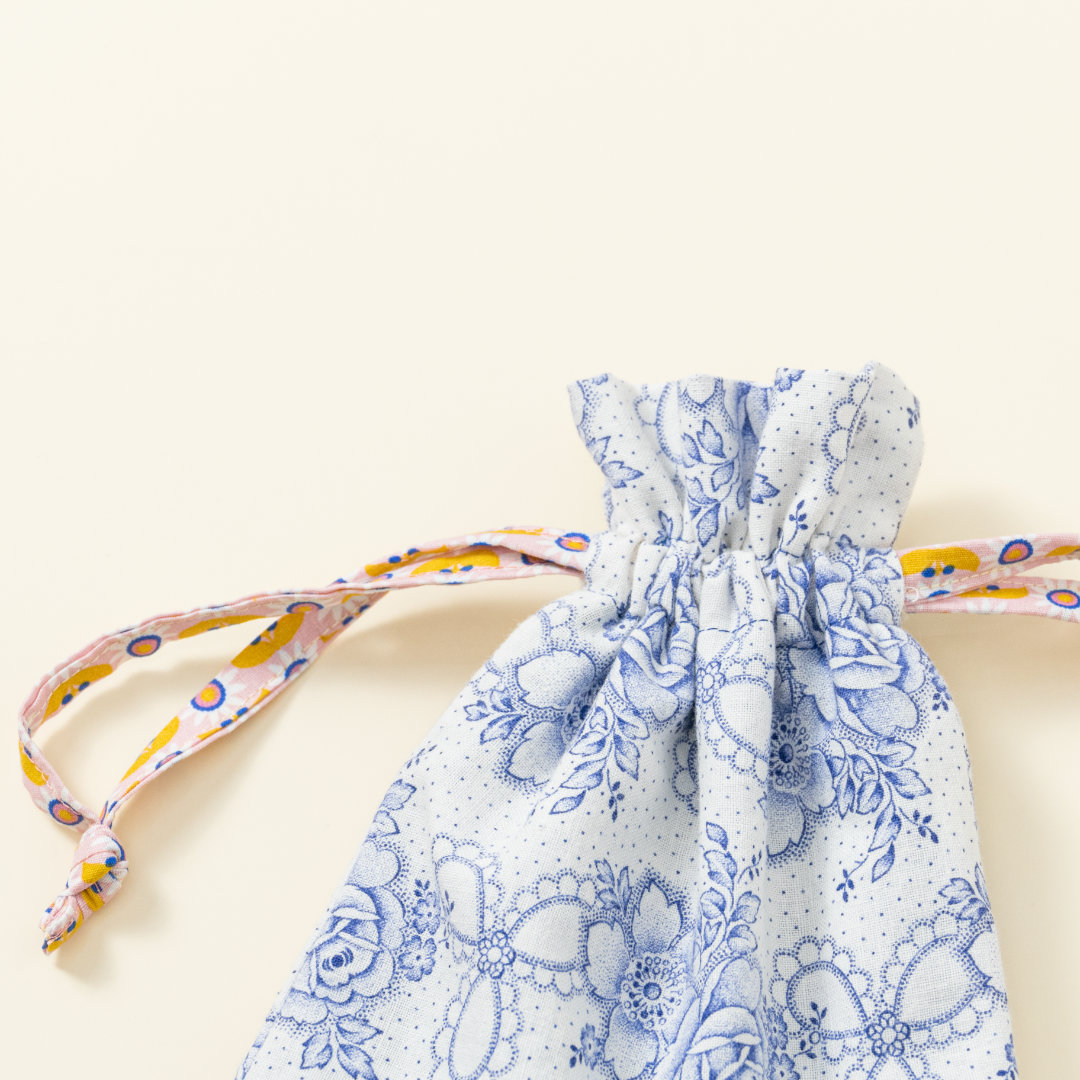 Hand-genähtes Murmelsäckchen mit Blumen-Muster in Weiß-Blau außen und gepunktet innen, geschlossen, inklusive einem individuellem Set aus einer großen Glas-Murmel und zwölf kleinen Glas-Murmeln, Detailaufnahme Bund Säckchen