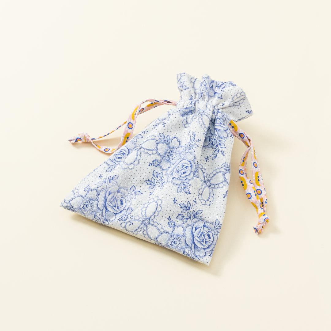 Hand-genähtes Murmelsäckchen mit Blumen-Muster in Weiß-Blau außen und gepunktet innen, geschlossen, inklusive einem individuellem Set aus einer großen Glas-Murmel und zwölf kleinen Glas-Murmeln