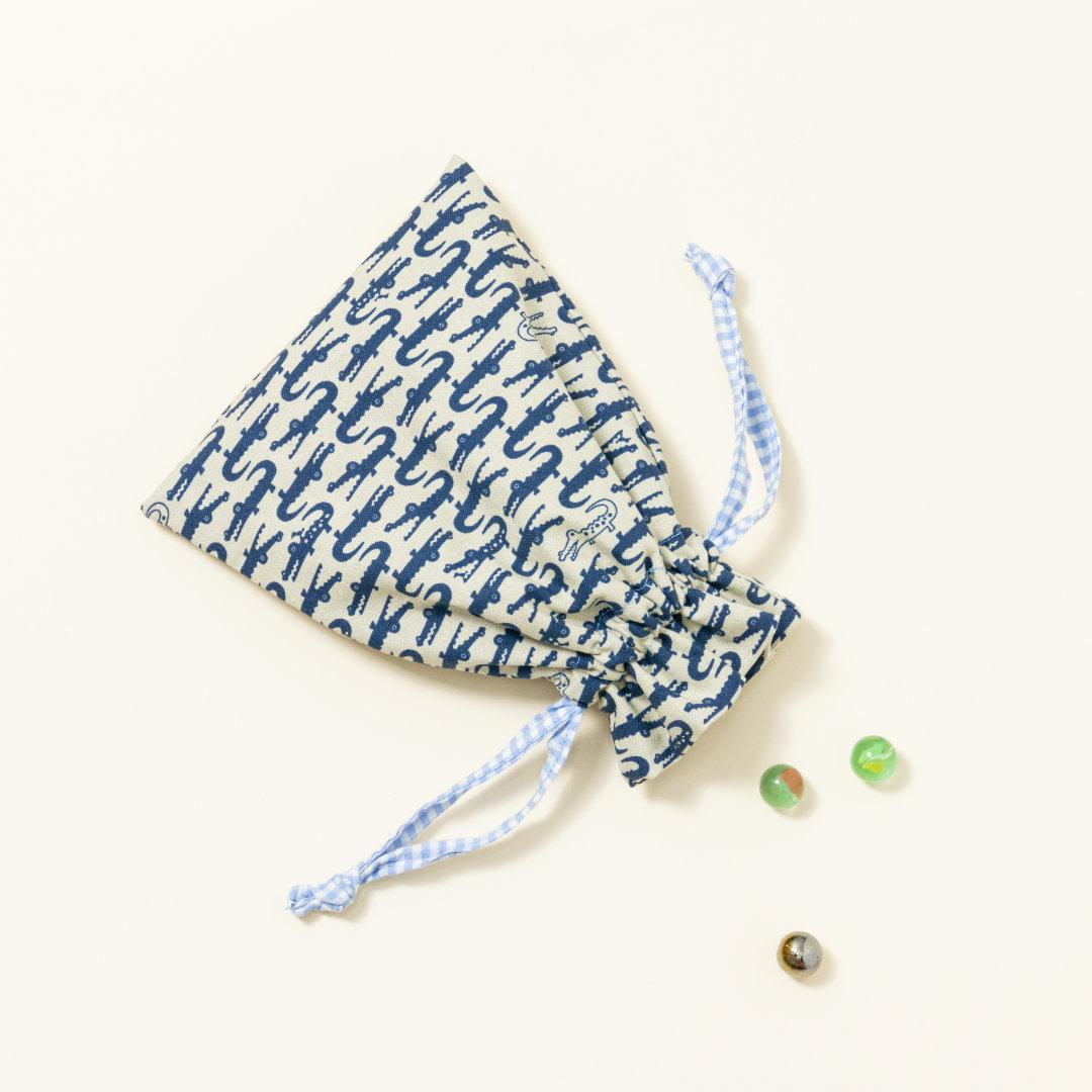 Hand-genähtes Murmelsäckchen mit Krokodil-Muster in Beige-Blau außen und kariert in Beige-Weiß innen, geschlossen, inklusive einem individuellem Set aus einer großen Glas-Murmel und zwölf kleinen Glas-Murmeln