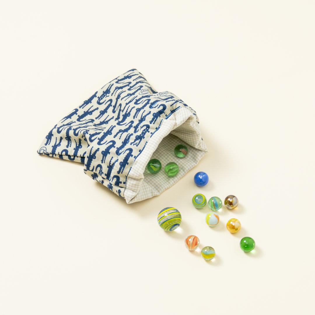 Hand-genähtes Murmelsäckchen mit Krokodil-Muster in Beige-Blau außen und kariert in Beige-Weiß innen, geöfffnet, inklusive einem individuellem Set aus einer großen Glas-Murmel und zwölf kleinen Glas-Murmeln