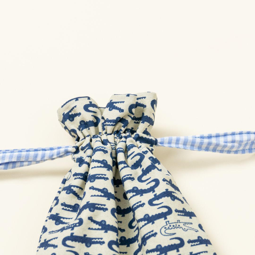 Hand-genähtes Murmelsäckchen mit Krokodil-Muster in Beige-Blau außen und kariert in Beige-Weiß innen, geschlossen, inklusive einem individuellem Set aus einer großen Glas-Murmel und zwölf kleinen Glas-Murmeln, Detailaufnahme Bund Säckchen