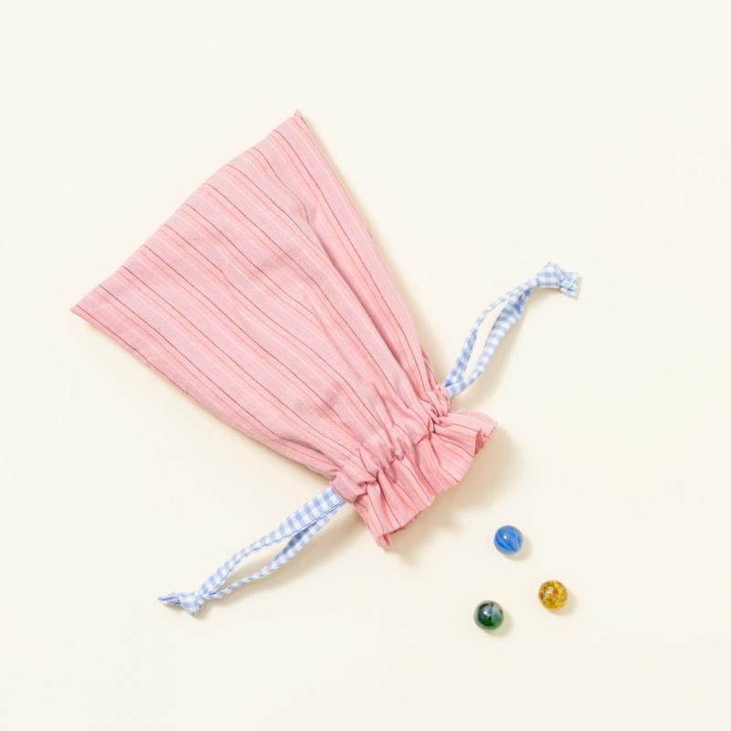 Hand-genähtes Murmelsäckchen mit Streifen-Muster in Rosa außen und gepunktet in Beige-Schwarz innen, geschlossen, inklusive einem individuellem Set aus einer großen Glas-Murmel und zwölf kleinen Glas-Murmeln