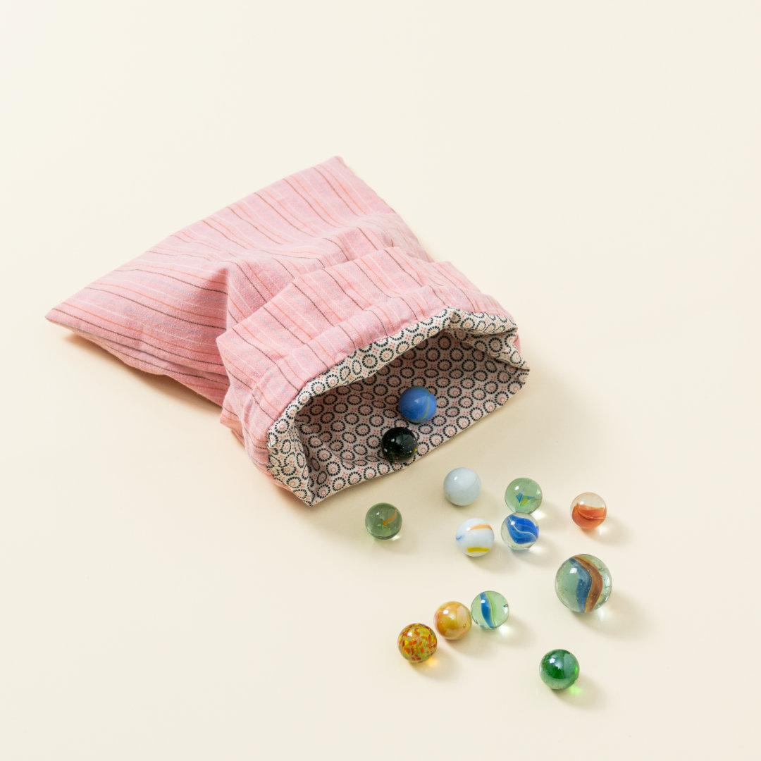 Hand-genähtes Murmelsäckchen mit Streifen-Muster in Rosa außen und gepunktet in Beige-Schwarz innen, geöffnet, inklusive einem individuellem Set aus einer großen Glas-Murmel und zwölf kleinen Glas-Murmeln
